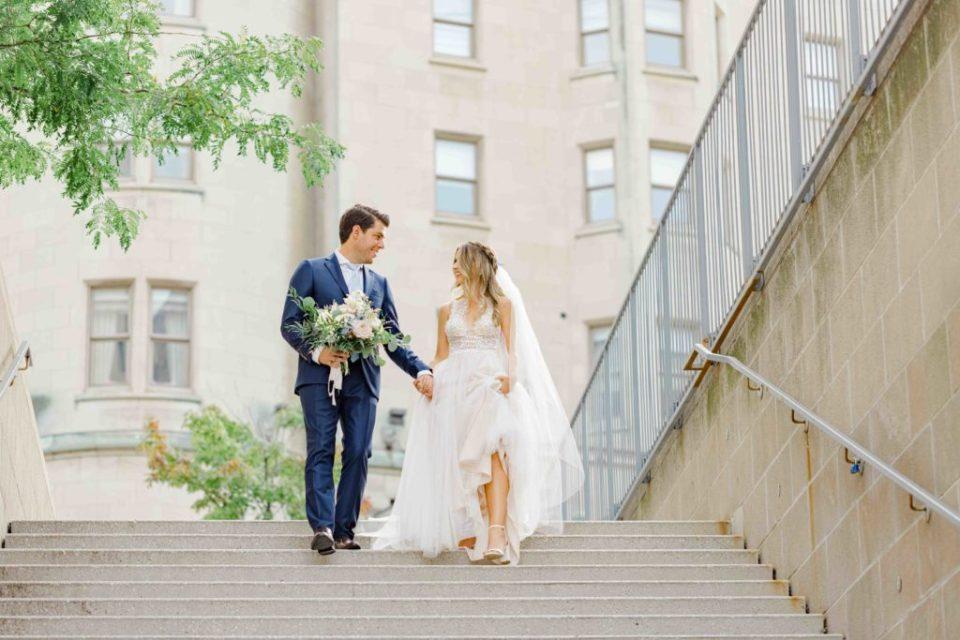 Bride and Groom walking down steps near Chateau Laurier Downtown Ottawa in Summer. Blue Suit, big floral bouquet, beautiful braided & curled hair. Grey Loft Studio -Ottawa Wedding Photographer
