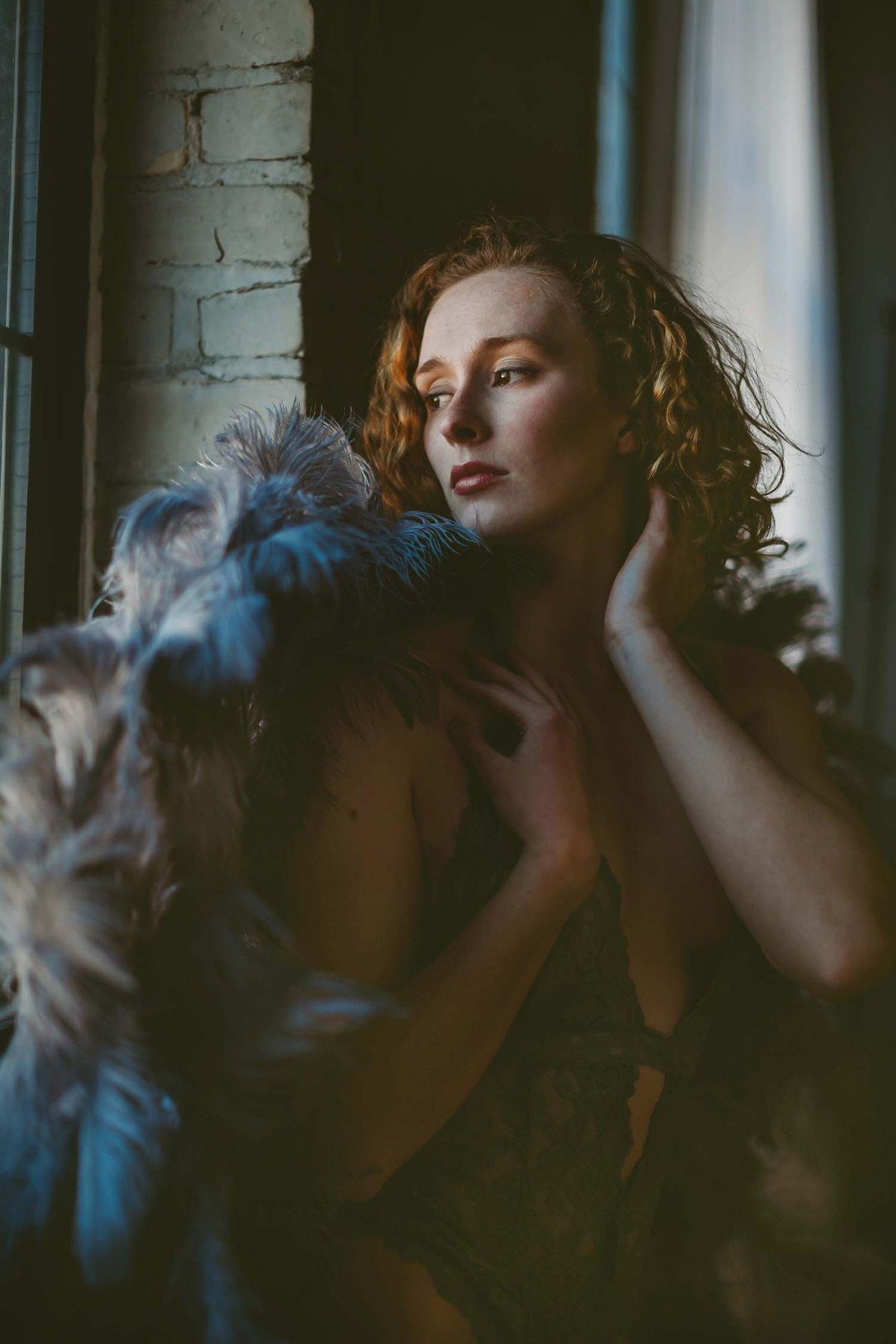 Woman dark moody portrait window natural light wings Minneapolis MN Minnesota photo studio