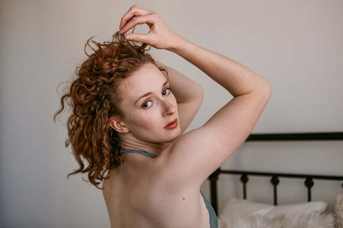 light an airy intimate portrait lifestyle wearing angel wings prop Saint Paul, natural light photography . Midwest Boudoir Photographers