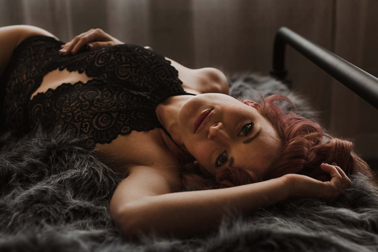 Lifestyle intimate portrait on bed with faux fur throw.  Minneapolis Boudoir Photographer