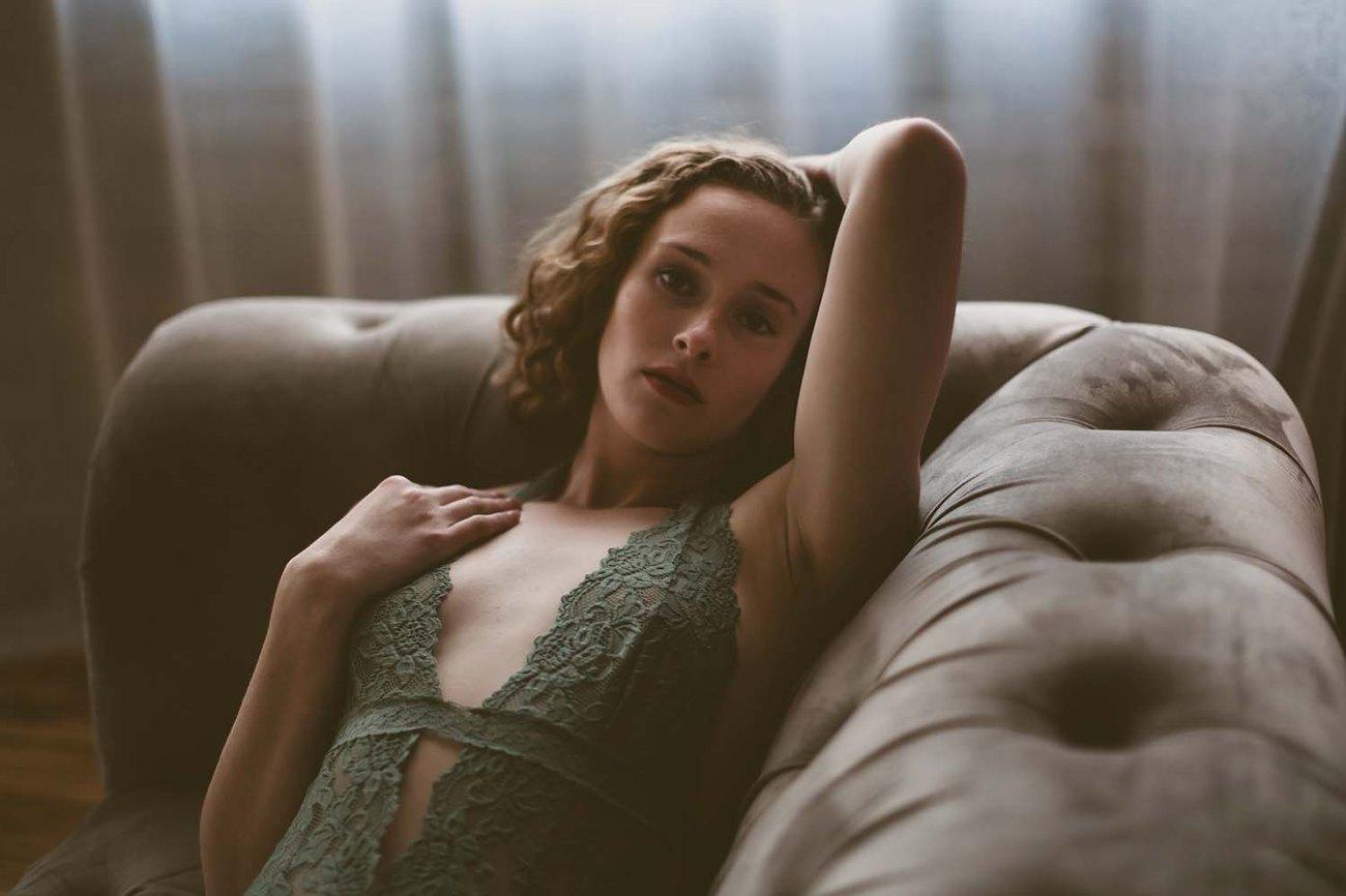 Beautiful woman in green seafoam, lace bodysuit lays on couch, sensual boudoir portrait. St Paul boudoir photo shoot