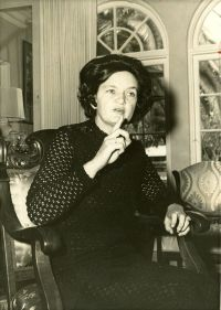 A sepia photo of a dark-haired woman sitting in a chair