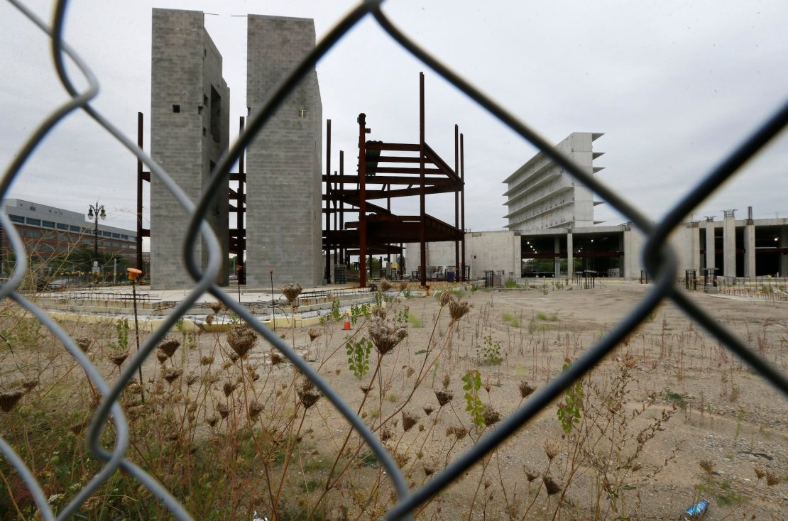 as seen through a fence, a construction site with a pair of tall concrete pillars and a lot overgrown with weeds