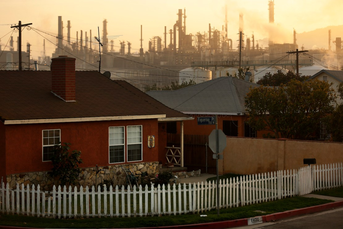A sprawling refinery in the background of a row of residential homes.