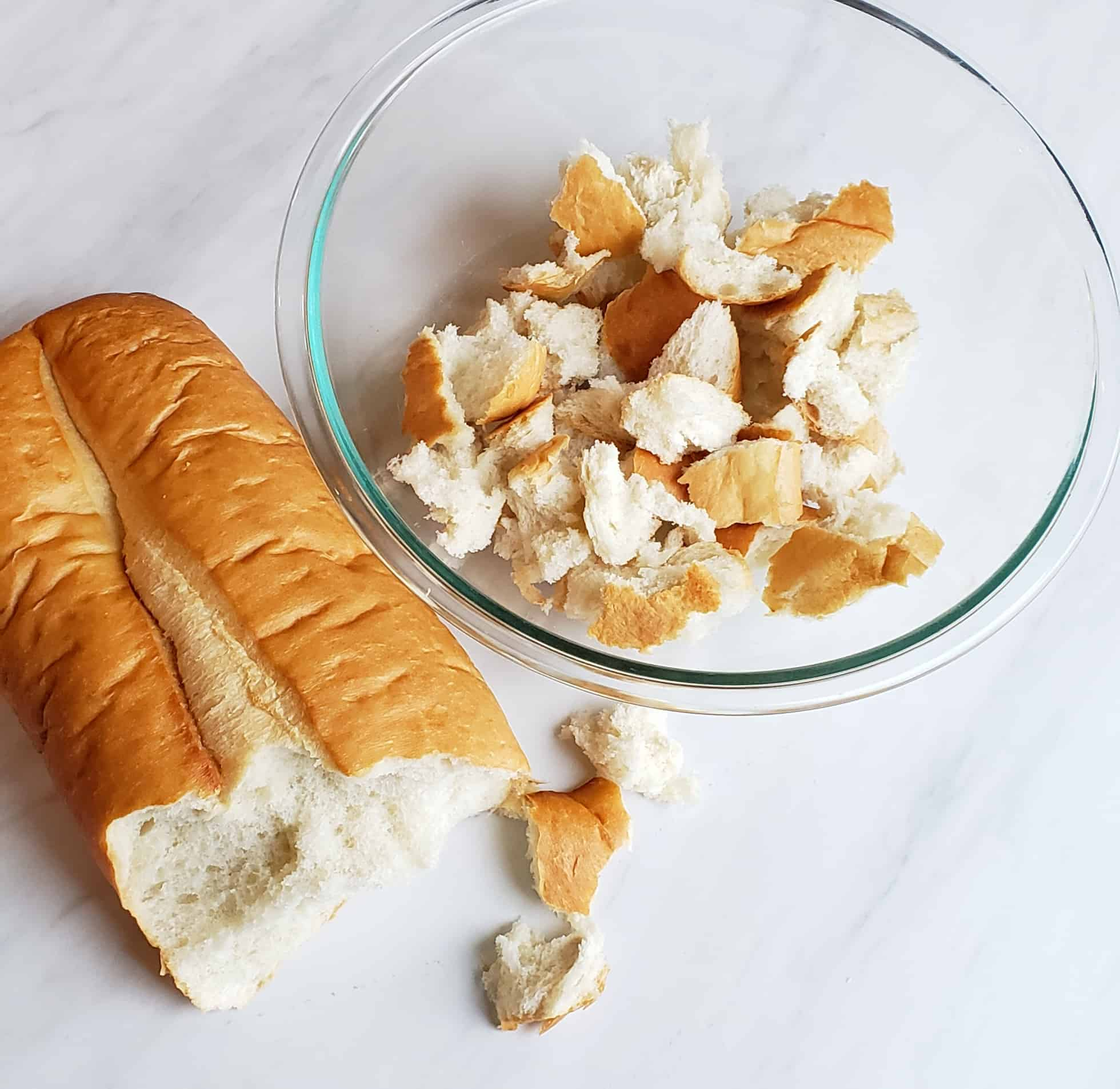 loaf of french bread being torn in a clear glass bowl