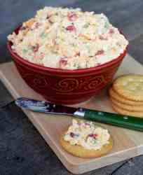 Pimiento Cheese with cream cheese and chopped jalapeno peppers in a red bowl and a little spread on a Ritz cracker with a green spreader