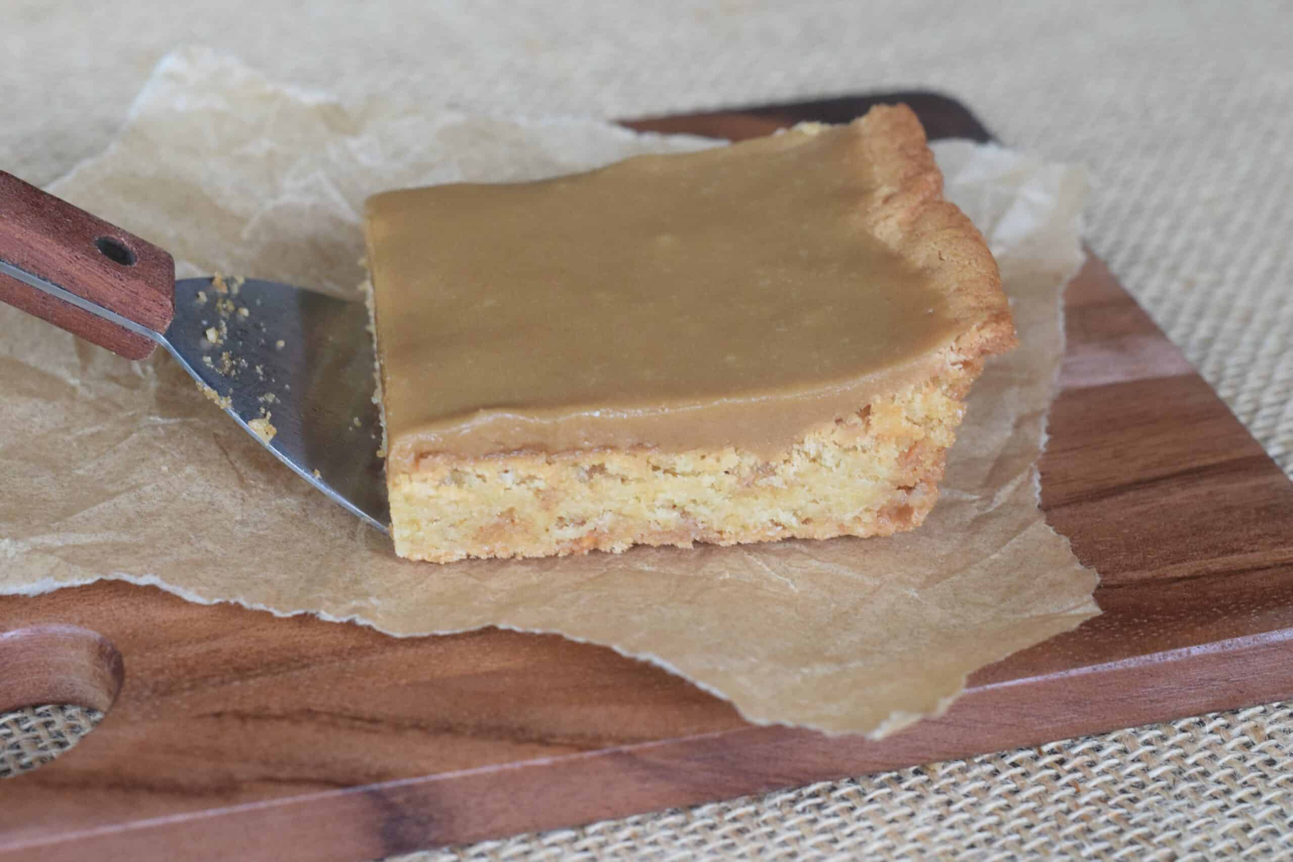 Toffee Blonde Brownies with Cheaters Caramel Icing served on a dark brown wooden cutting board with a metal spatula