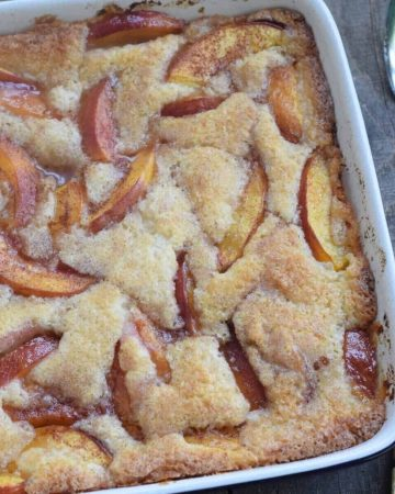 Nectarine cobbler in square blue dish with antique spoon