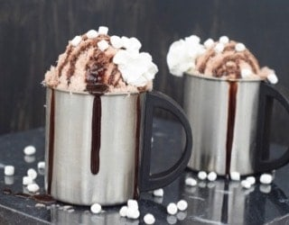 Two silver mugs of chocolate snow ice cream with chocolate drizzle coming down the side.