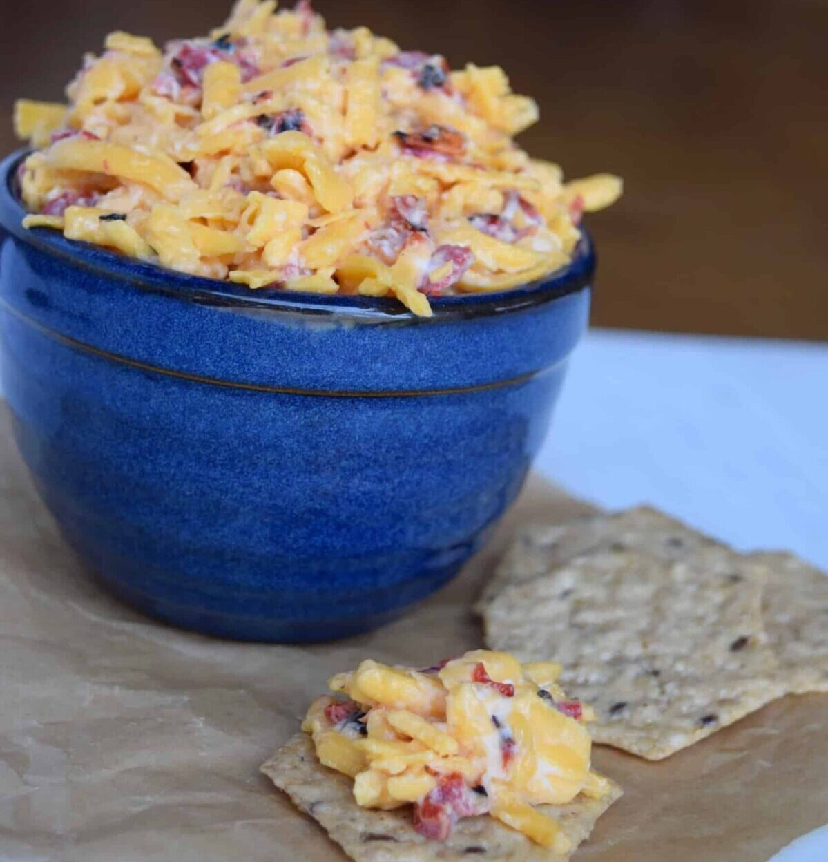 Pimiento Cheese in a blue bowl and on a cracker