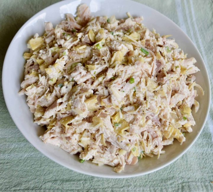 chicken salad with artichokes in a white rimmed plate