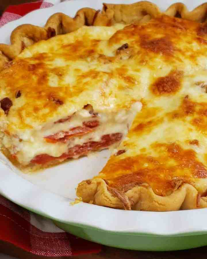 Tomatoes and onion pie layered with slice out in a fluted white and green pie dish