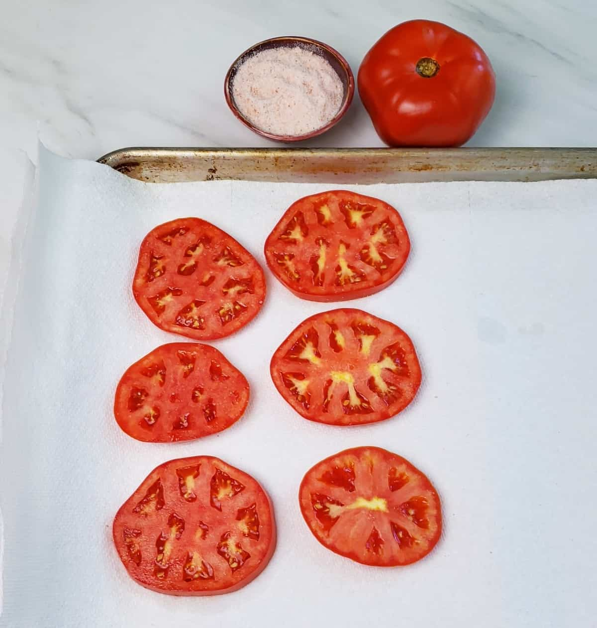 sliced tomatoes on paper towels on a baking pan. A tiny dish of pink salt and a tomato is next to pan