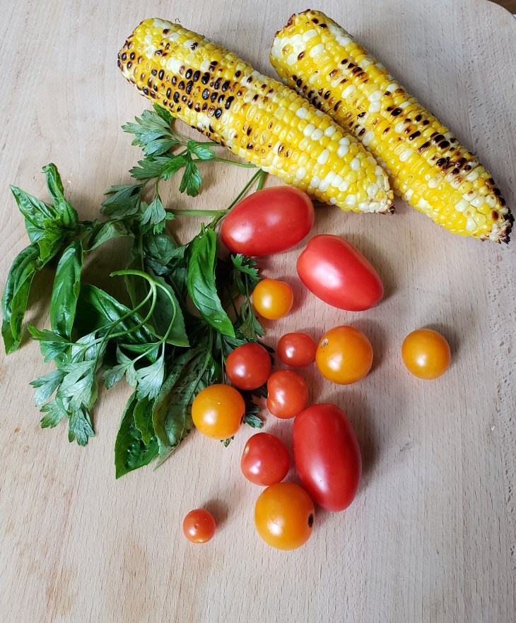 Roasted corn, red and yellow grape tomatoes, basil and parsley on wooden surface