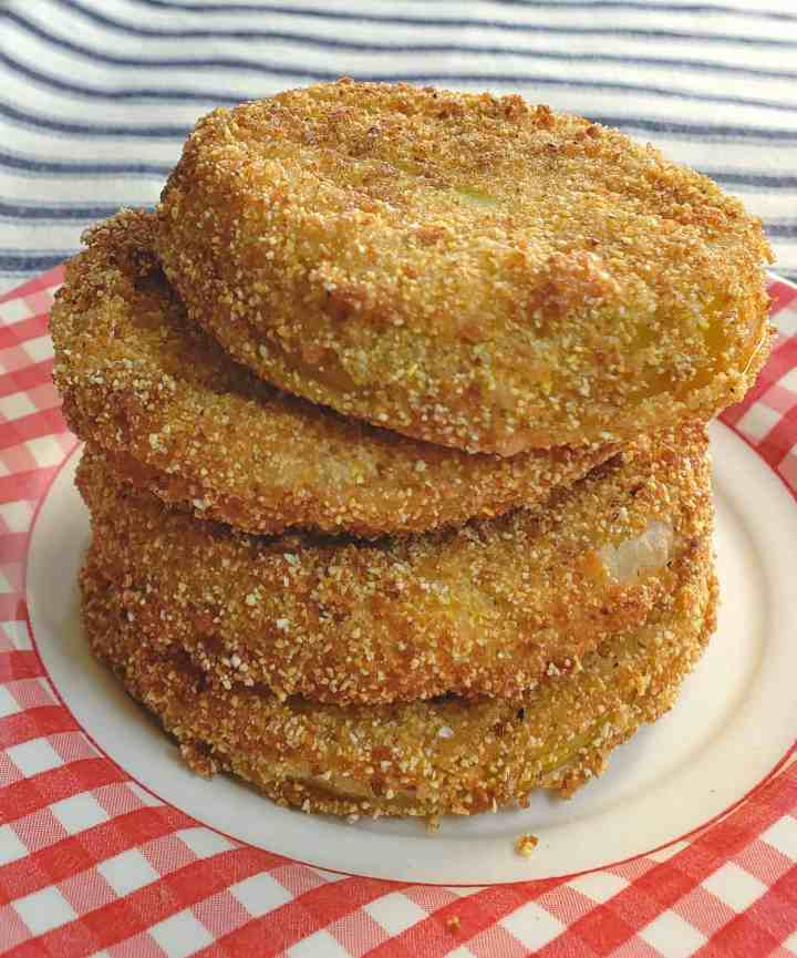 four fried green tomatoes stacked on red checkered plate