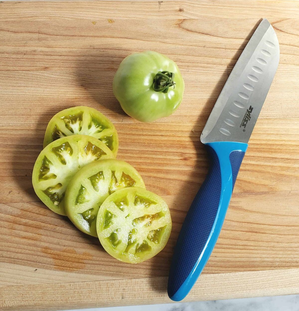 Sliced green tomatoes with knife on cutting board