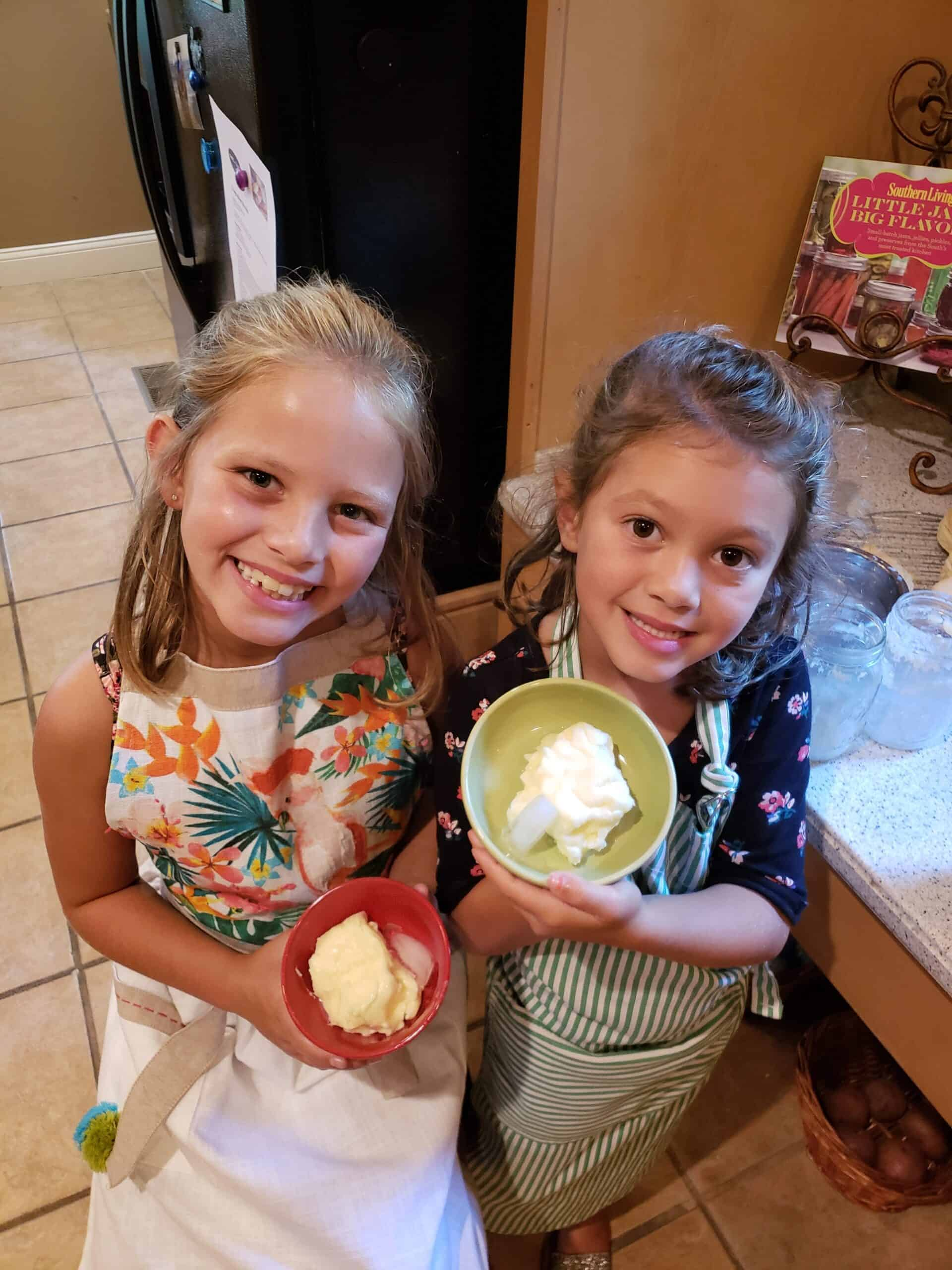 Two girls in aprons holding bowls of homemade butter