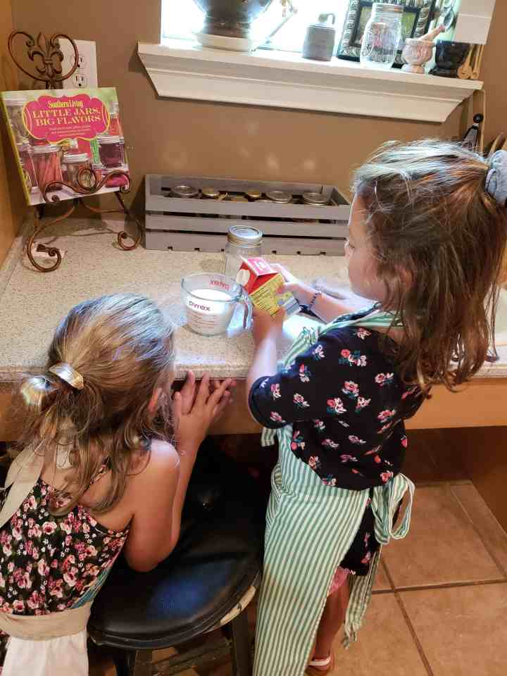 Little girls measuring whipping cream in a liquid measuring cup