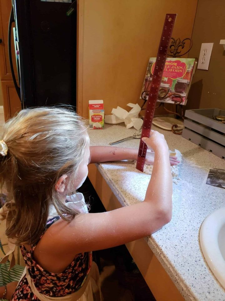 Girl measuring biscuit dough 3/4 inch thick