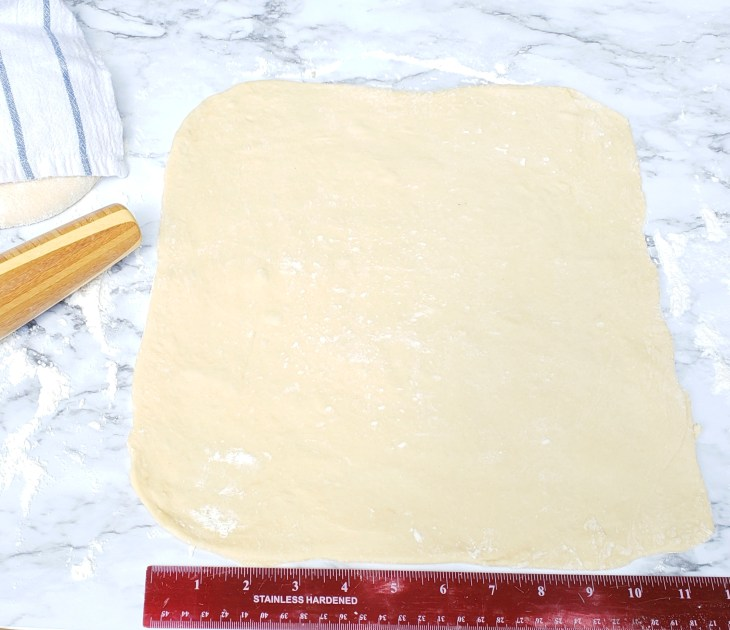 Cinnamon Roll dough rolled out with ruler and rolling pin