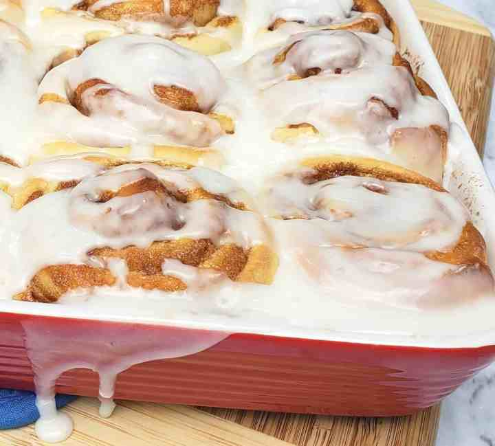 Cinnamon rolls in red baking dish with icing drip