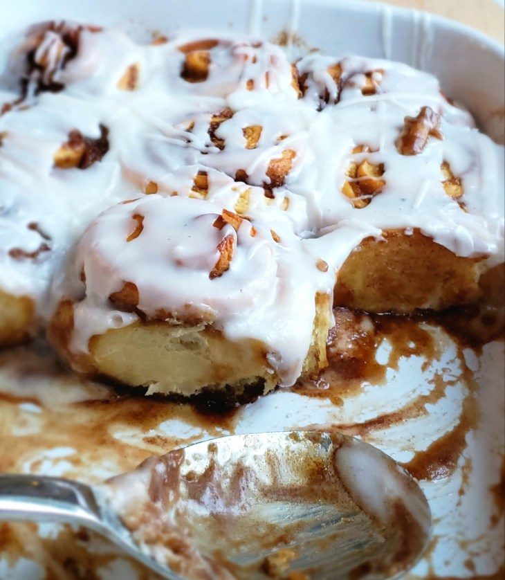 Double Stuffed Cinnamon Rolls. Made with double the brown sugary butter mixture in the middle. Cinnamon rolls removed with spoon in dish to show cinnamon mixture in the middle