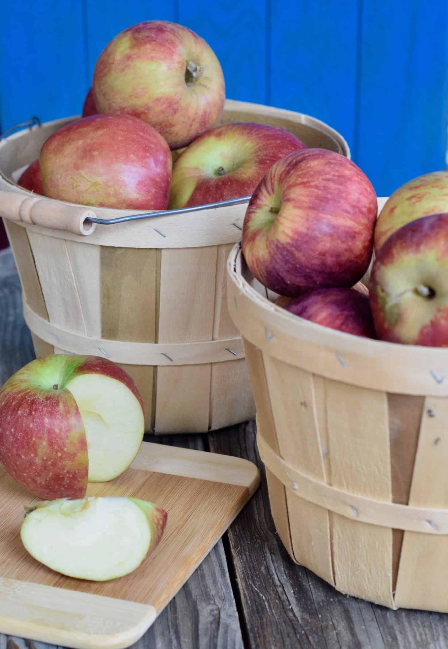 Apples in bushel basket with 1 sliced open