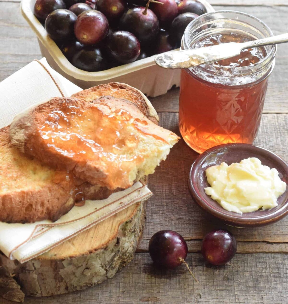 scuppernong jelly in a jar with knife resting on it, buttered bread with jelly on a log slice, muscadine grapes on a wooden surface