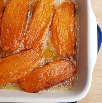 sweet potatoes cut in half lengthwise candied in white casserole dish