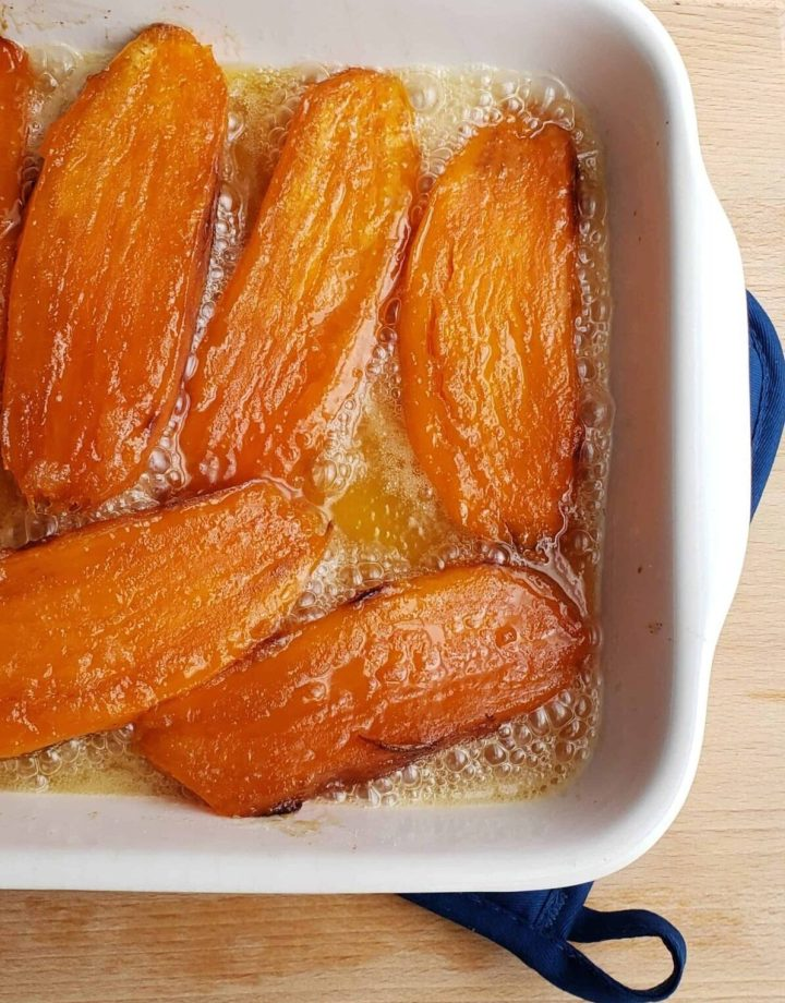 sweet potatoes cut in half lengthwise candied in white casserole dish. Southern side dish
