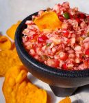 Cranberry Apple Jalapeno Salsa in a black salsa dish with sweet potato chips in it and around the dish