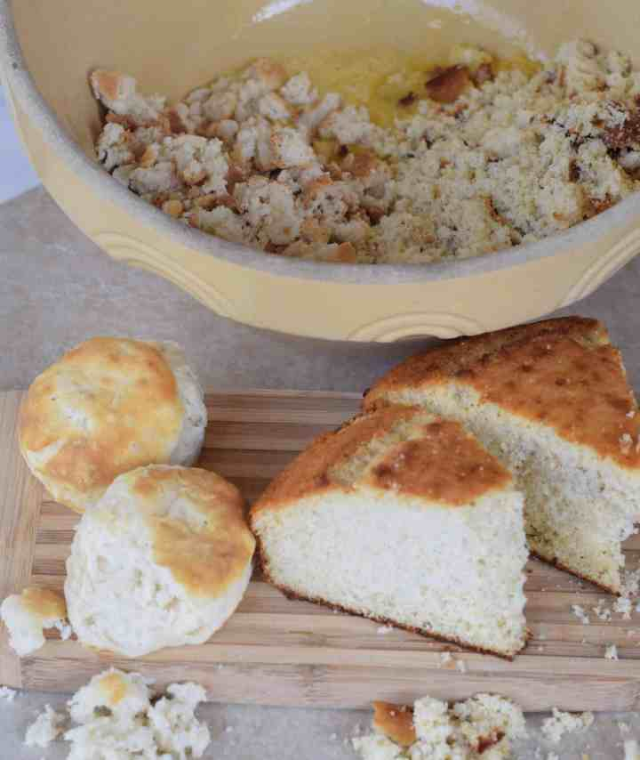 cornbread slices and 2 biscuits on wooden cutting board with bread crumbled in bowl