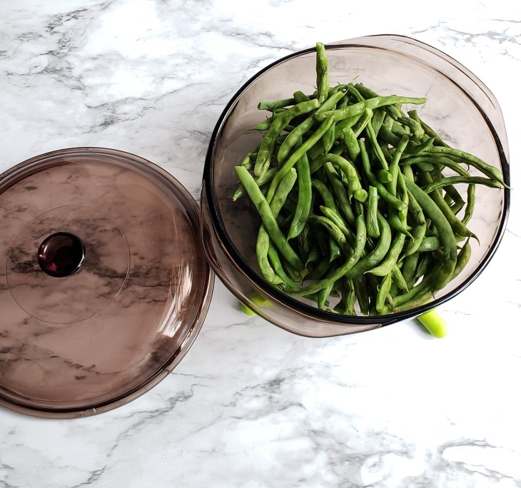 Fresh green beans steamed in a dark pyrex bowl with the lid on a marble surface.