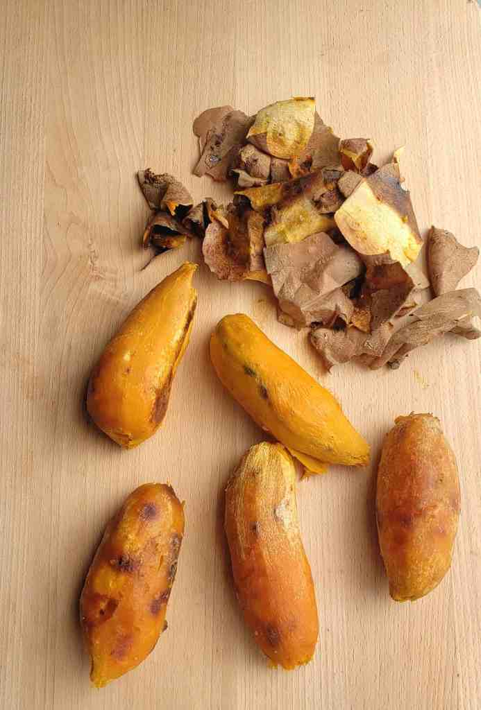 5 peeled roasted sweet potatoes on a wooden surface with peels in a pile