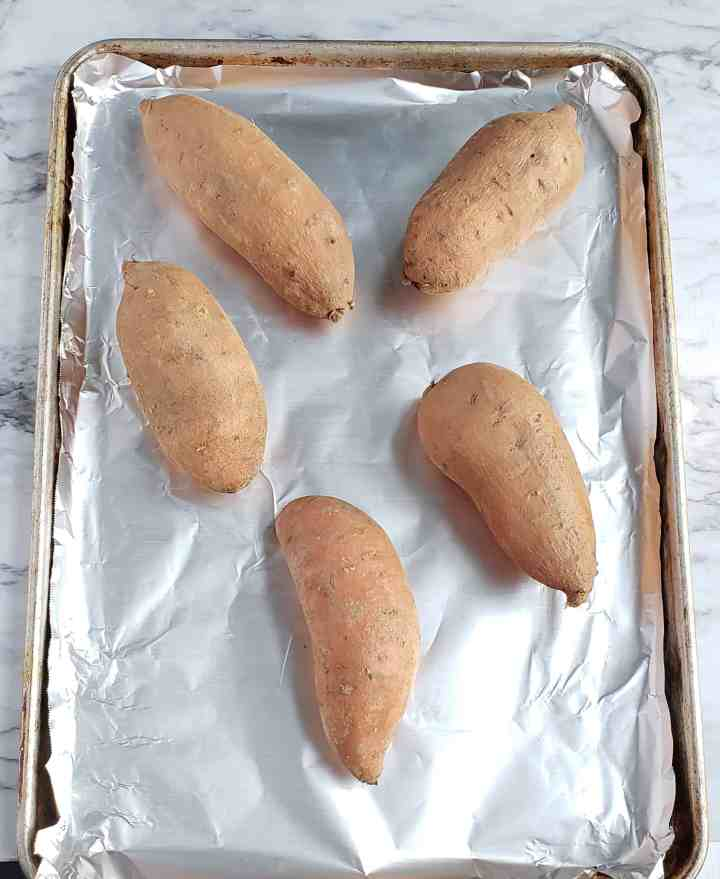 5 sweet potatoes on a foil-lined baking sheet