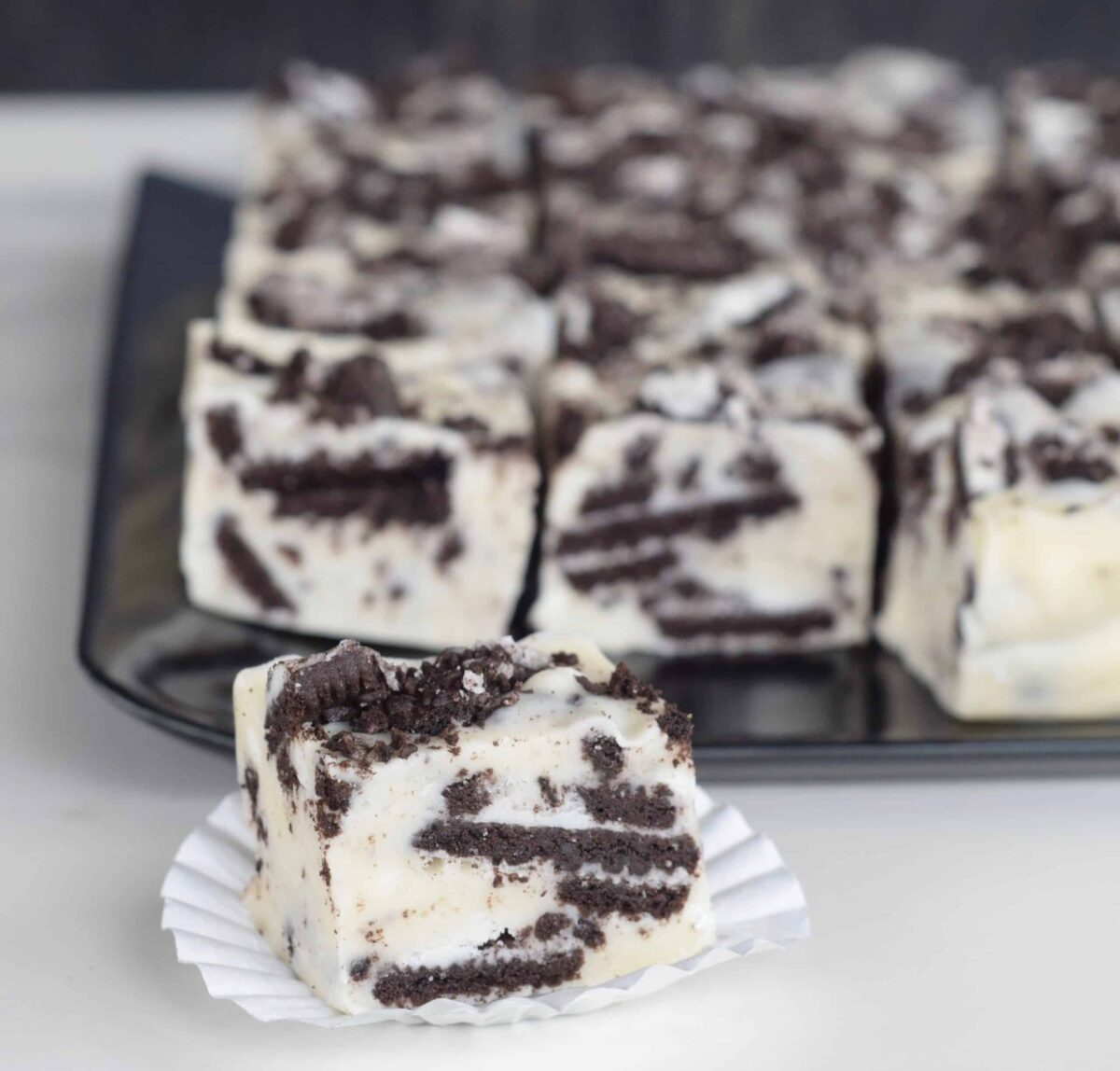 Cookies n Cream White Chocolate Fudge. No Candy thermometer needed! A black platter of fudge with one on a white candy wrapper