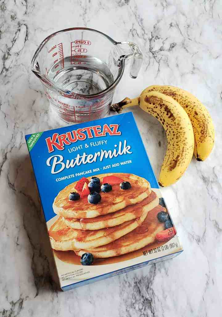 pancake mix Krusteaz and measuring cup of water bananas on marble surface