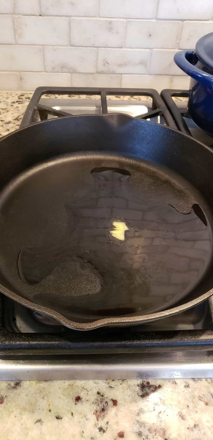 cast iron skillet on stovetop with butter and oil melting in it