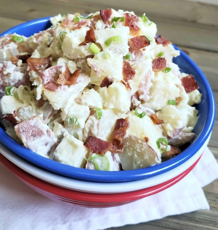 Sour Cream and Green Onion Potato Salad in a stack of 3 red, white and blue bowls on white cloth