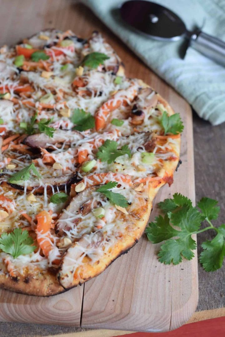 Chicken Grilled Pizza on wooden cutting board with pizza wheel on green cloth with fresh cilantro garnish