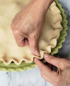 Crimping is just one way to finish the pie crust edges but it's my favorite. Gently push the pie dough edge with your thumb into two of your fingers that are put together as if to pinch something.