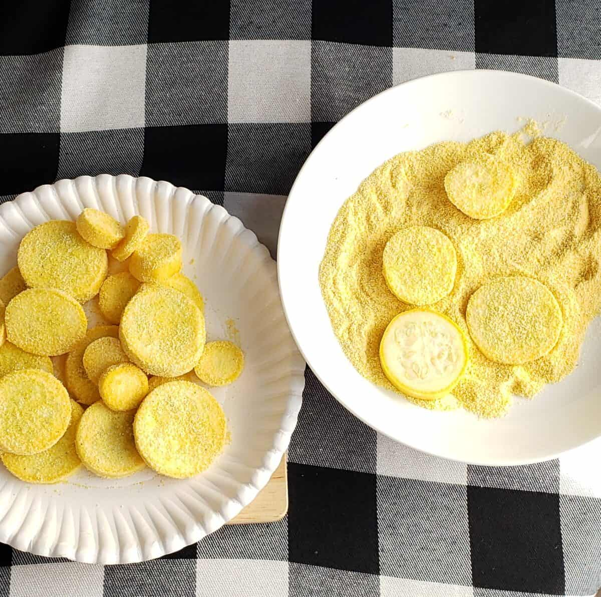 Coating yellow squash in cornmeal on white paper plates on black and white checkered fabric