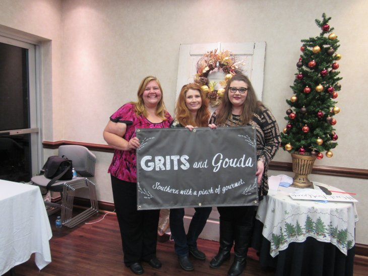 Guests holding up Grits and Gouda banner by selfie station