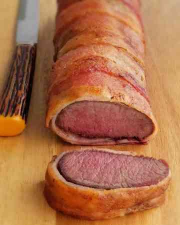Bacon wrapped venison roast on cutting board. slice cut. steak knife