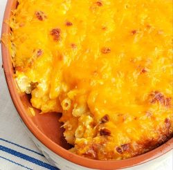 Macaroni and cheese in tan dish with scoop out