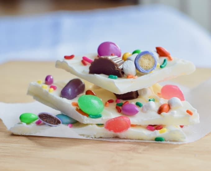 3 stacked pieces of Easter chocolate bark on wooden surface