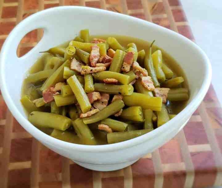 green beans with bacon in a white bowl on a checkered cutting board