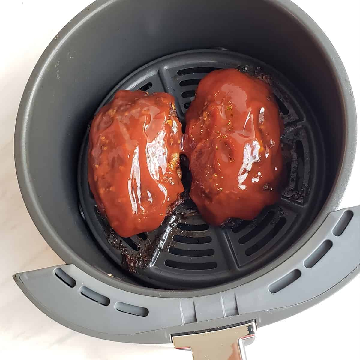 Topping Best Air Fryer Meat Loaf with Tangy Sauce in the air fryer