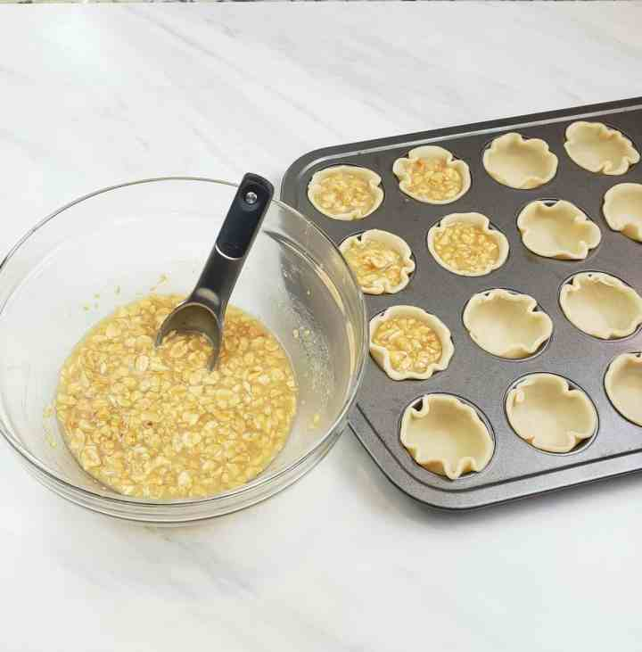 mini peanut pies in muffin pans before baking with bowl of filling