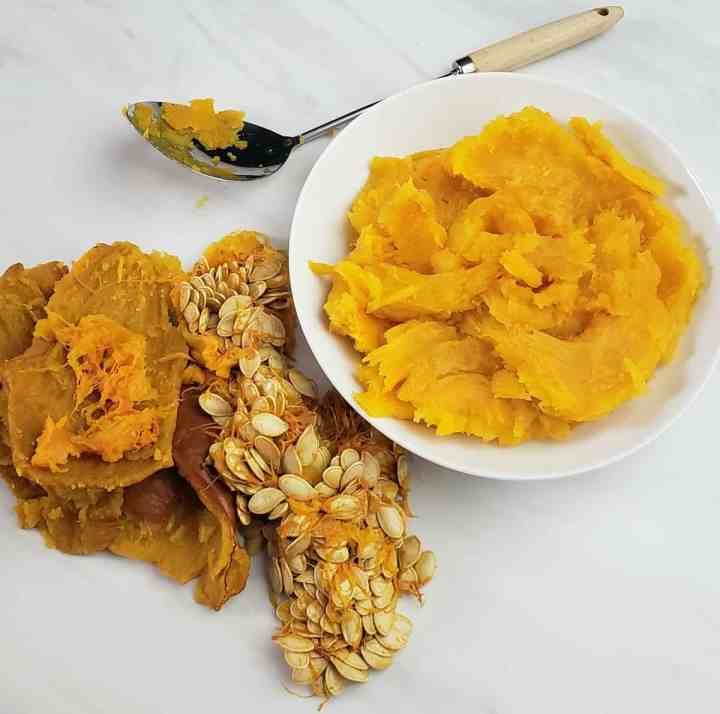 Pumpkin seeds and rind on white surface; puree in white bowl